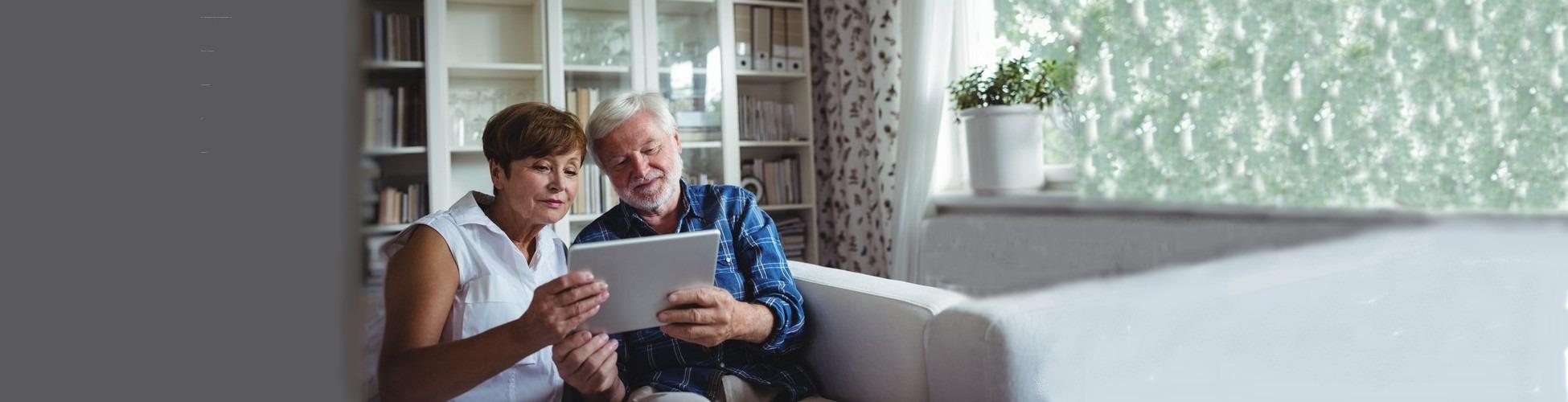 slider couple senior qui suit ses comptes ses revenus et ses dépenses sur tablette