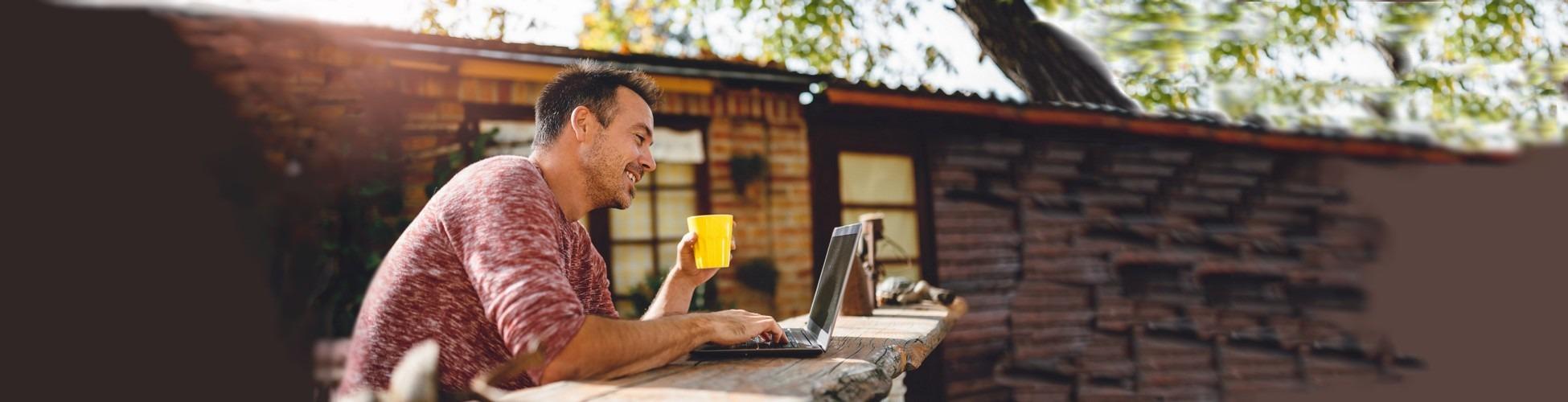 slider homme qui gère ses comptes et placements en ligne avec un logiciel de budget à l'extérieur sur son portable