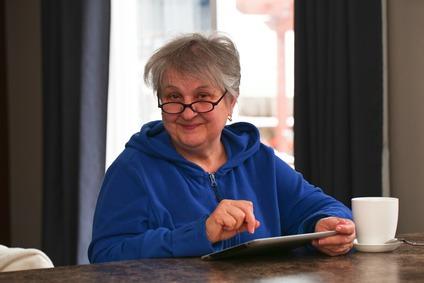 senior sympathique mamie 60-ans fait ses comptes sur tablette